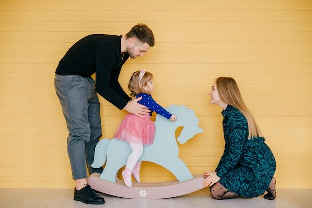Gelukkig jong gezin met een kind plezier samen over gele muur