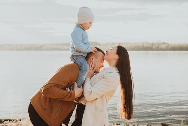Gelukkig jong gezin met hun zoon op het strand aan de rivier in de zomer