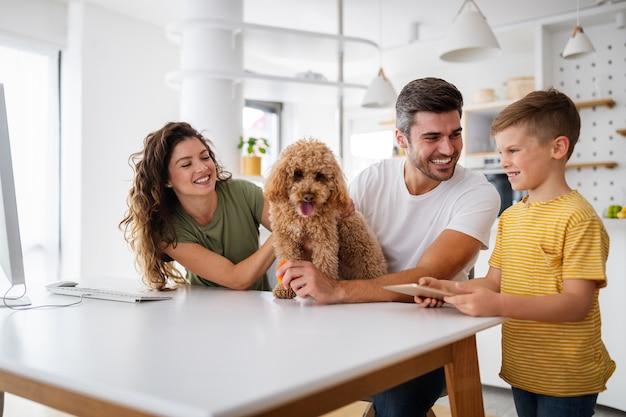 Gelukkig jong gezin met moderne apparaten en hond die plezier heeft, thuis speelt