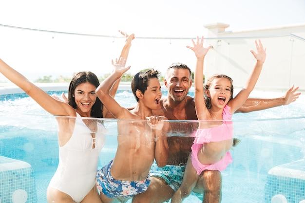 Gelukkig jong gezin met plezier in een zwembad