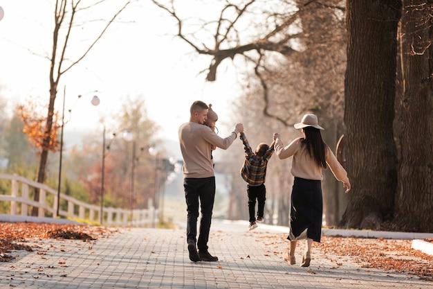 Gelukkig jong gezin met twee kleine kinderen wandelen en plezier maken in herfst park op zonnige dag