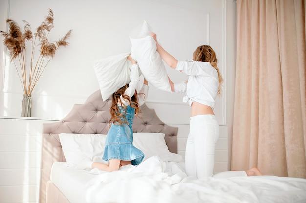 Gelukkig jong gezin mooie moeder en dochter spelen op het bed en kussen, tijd samen doorbrengen