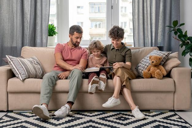 Gelukkig jong gezin van drie in vrijetijdskleding zittend op een comfortabele bank in gezellige huiselijke kamer bij raam en encyclopedie lezen