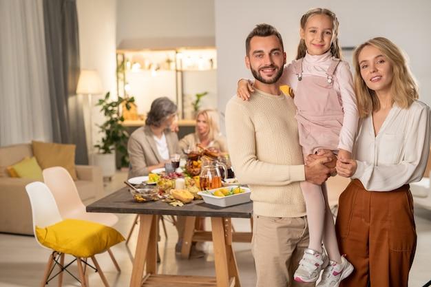Gelukkig jong gezin van vader, moeder en hun schattige dochtertje die naar je kijken met een glimlach op de achtergrond van een matue-paar aan een feestelijke tafel