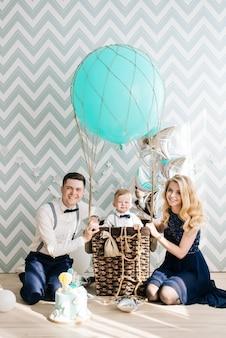 Gelukkig jong gezin viert de eerste verjaardag van het kind. de baby is 1 jaar oud. het concept van een kinderfeestje met ballonnen