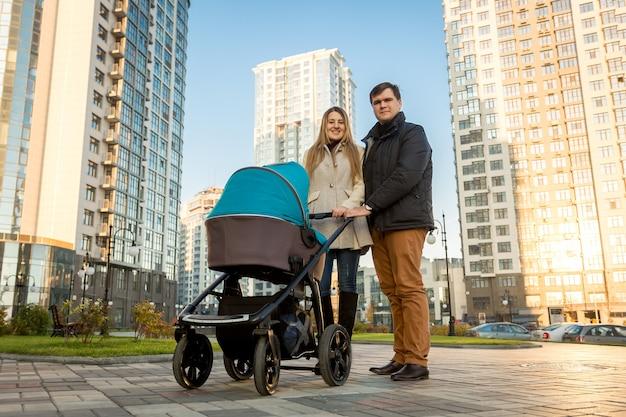 Gelukkig jong gezin wandelen met kinderwagen op straat op zonnige dag