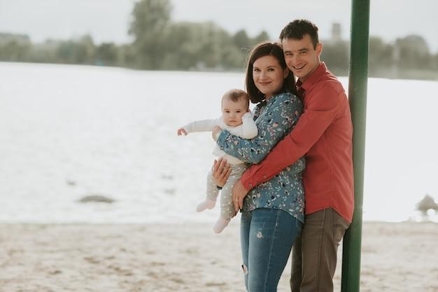 Gelukkig jong gezin zitten in de buurt van het water