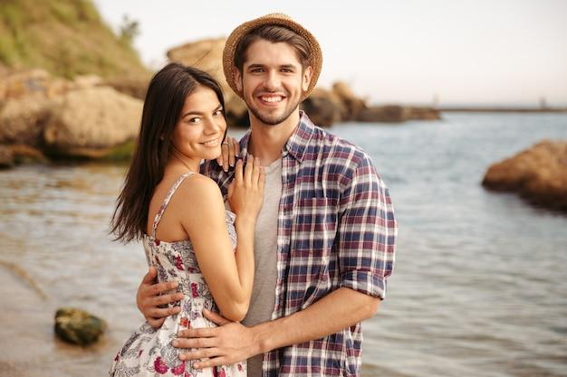 Gelukkig jong hipsterpaar dat verliefd op het strand staat en knuffelt