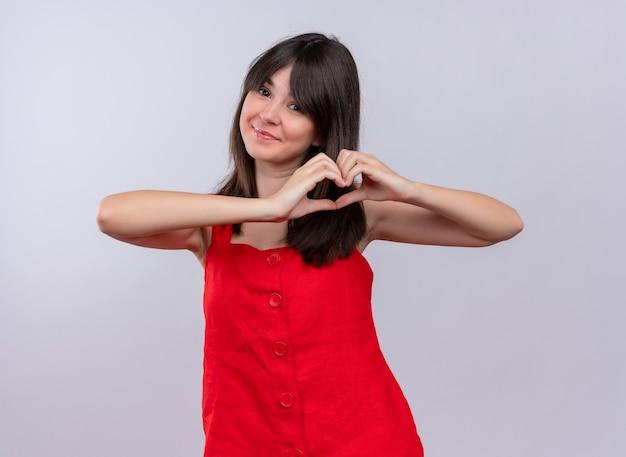 Gelukkig jong kaukasisch meisje dat een hartgebaar met beide handen doet en camera op geïsoleerde witte achtergrond bekijkt