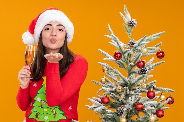 Gelukkig jong kaukasisch meisje met kerstmuts houdt glas champagne vast en stuurt een kus met de hand staande naast de kerstboom geïsoleerd op een oranje achtergrond met kopie ruimte
