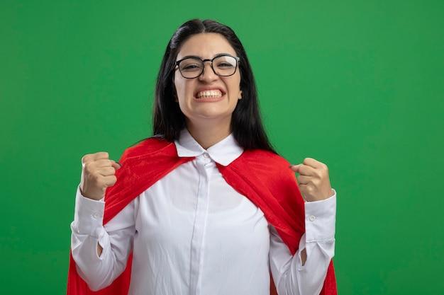 Gelukkig jong kaukasisch superheromeisje die glazen glimlachen en gebalde vuisten dragen die op groene muur met exemplaarruimte worden geïsoleerd