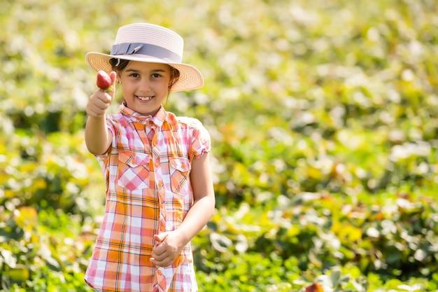 Gelukkig jong kindmeisje dat aardbeien plukt en eet op een plantage