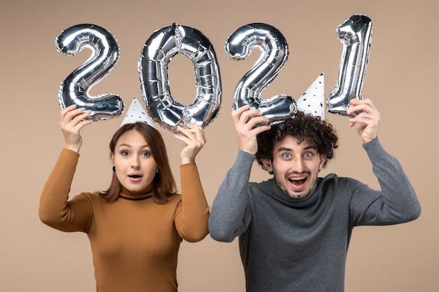 Gelukkig jong koppel dragen nieuwe jaar hoed vormt voor camera meisje en en jongen met tonen en zetten ze op hun hoofd op grijs