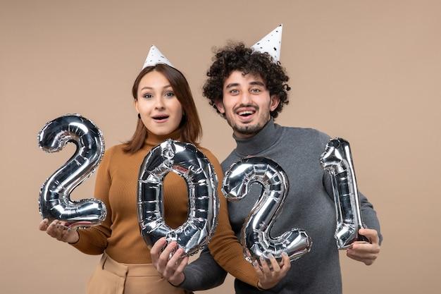 Gelukkig jong koppel dragen nieuwe jaar hoed vormt voor de camera samen meisje nemen en jongen met en op grijs