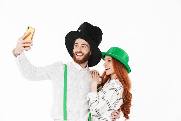 Gelukkig jong koppel gekleed in kostuums, vieren stpatrick's day geïsoleerd over witte muur, een selfie nemen