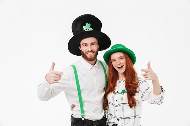 Gelukkig jong koppel gekleed in kostuums, vieren stpatrick's day geïsoleerd over witte muur, wijzende vingers