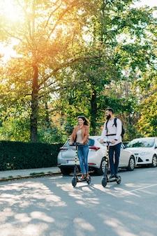 Gelukkig jong koppel genieten samen tijdens het rijden op elektrische scooters op straat in de stad.