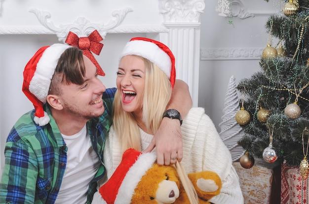Gelukkig jong koppel in cacsual kleding en grappige hoeden vieren kerstmis