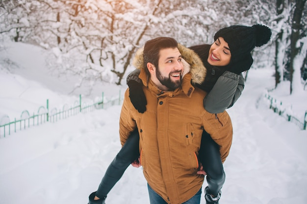 Gelukkig jong koppel in de winter. familie buitenshuis. man en vrouw naar boven kijken en lachen. liefde, plezier, seizoen en mensen - wandelen in winterpark. sta op en houd elkaars handen vast. zij op zijn rug.