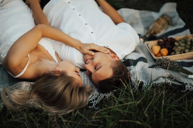 Gelukkig jong koppel in het park is ontspannen tijdens de zomerpicknick. ze liggen op een deken op groen gras, kijken elkaar aan en glimlachen.