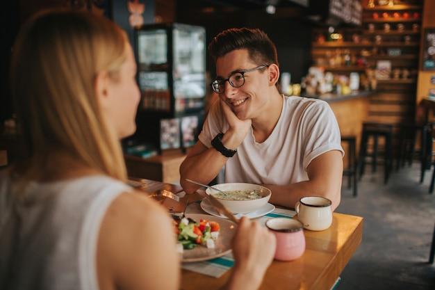 Gelukkig jong koppel in liefde met een leuke date in een bar of restaurant. ze vertellen wat verhalen over zichzelf, het drinken van thee of koffie en het eten van salade en soep.