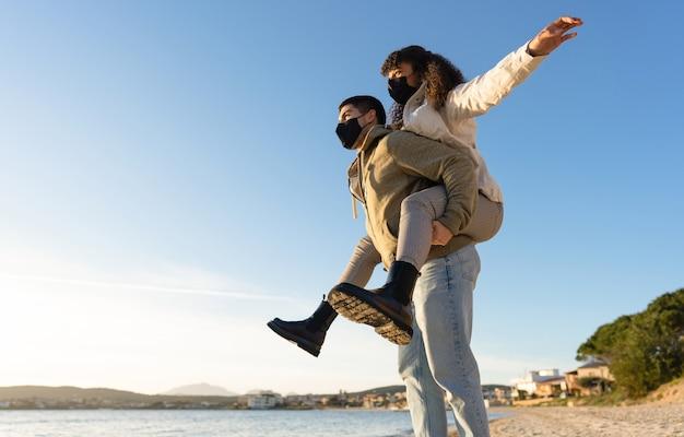 Gelukkig jong koppel in liefde met plezier doen meisje op meeliften op het strand in de wintervakanties met coronavirus beschermingsmasker bij zonsondergang.