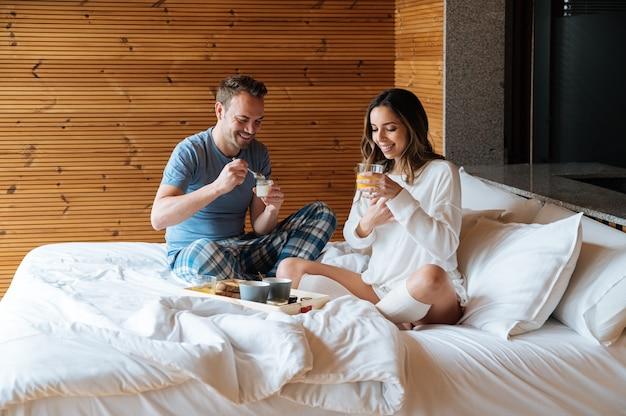 Gelukkig jong koppel in nachtkleding genieten van ontbijt op bed samen in gezellige slaapkamer met houten wand
