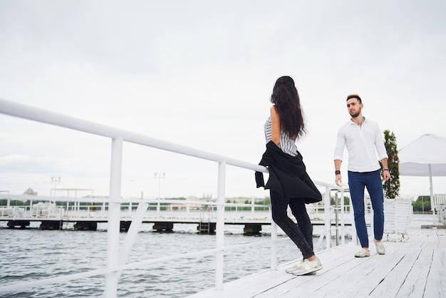 Gelukkig jong koppel in stijlvolle merkkleding, staande op de pier in het water.