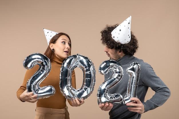 Gelukkig jong koppel kijken elkaar dragen nieuwe jaar hoed poses voor camera meisje en en jongen met en op grijs tonen