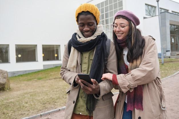 Gelukkig jong koppel kijken naar foto's op mobiele telefoon en lachen terwijl ze buiten wandelen