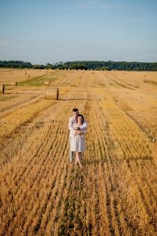 Gelukkig jong koppel knuffelen op stro veld