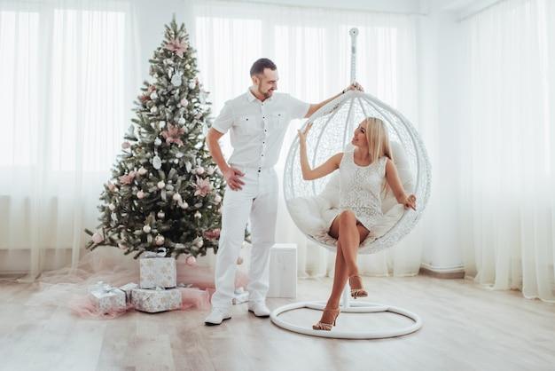 Gelukkig jong koppel met kerstmis, mooie geschenken en boom in de