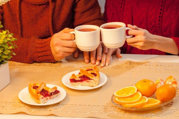 Gelukkig jong koppel met kopjes thee