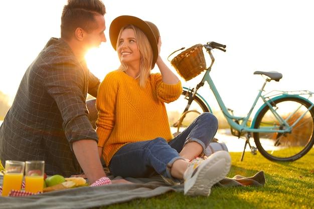 Gelukkig jong koppel met picknick buiten op zonnige dag