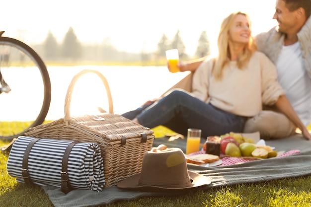 Gelukkig jong koppel met picknick in de buurt van meer, focus op rieten mand met deken en hoed
