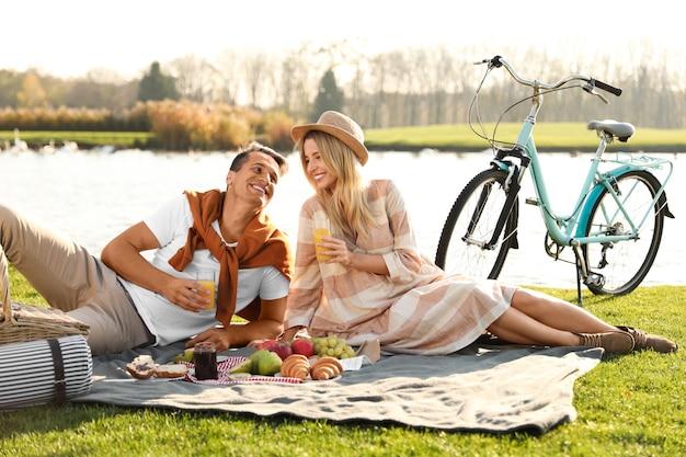 Gelukkig jong koppel met picknick in de buurt van meer op zonnige dag