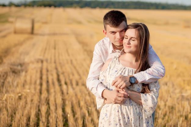 Gelukkig jong koppel op stro, romantisch mensenconcept, mooi landschap, zomerseizoen.