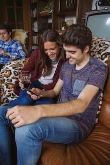 Gelukkig jong koppel op zoek naar smartphone zittend op een bank thuis