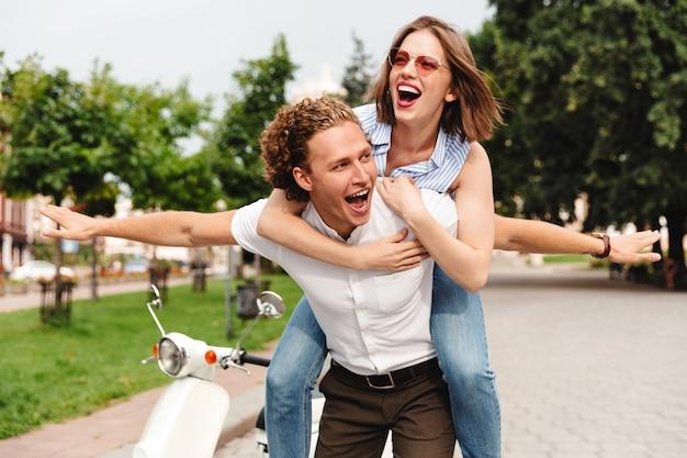 Gelukkig jong koppel plezier samen met scooter terwijl ze in het park