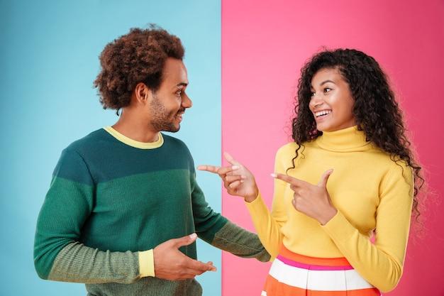 Gelukkig jong koppel praten en wijzen op elkaar over kleurrijke achtergrond