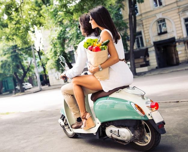 Gelukkig jong koppel rijden op een scooter terwijl vrouw met een boodschappentas vol boodschappen