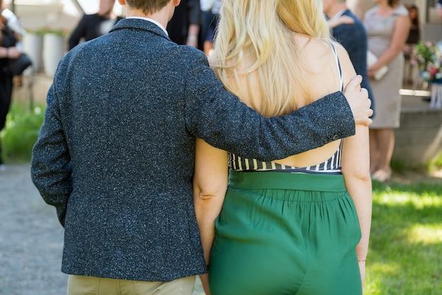 Gelukkig jong koppel van achteren, man is zijn vriendin knuffelen.