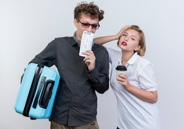 Gelukkig jong koppel van toeristen man en vrouw met koffer en vliegtickets met ernstige zelfverzekerde uitdrukking staande over witte muur