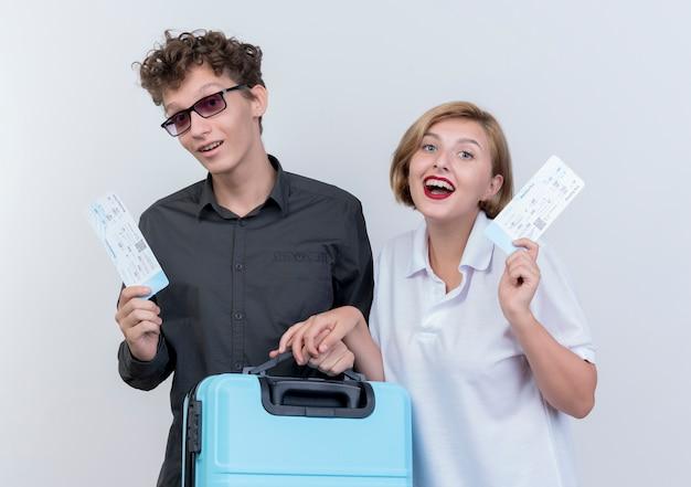 Gelukkig jong koppel van toeristen man en vrouw met vliegtickets en koffer staande over witte muur