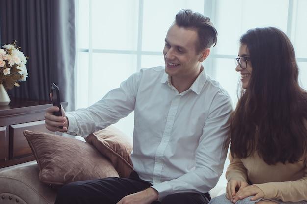 Gelukkig jong koppel zittend op een bank thuis, met behulp van mobiele telefoon