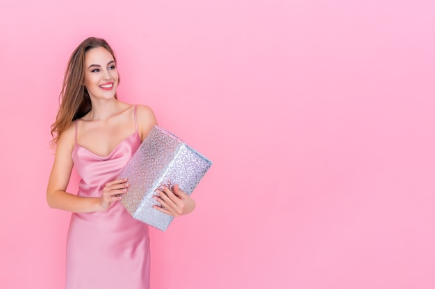 Gelukkig jong lachend meisje houdt geschenkdoos op geïsoleerde roze studio achtergrond viering concept