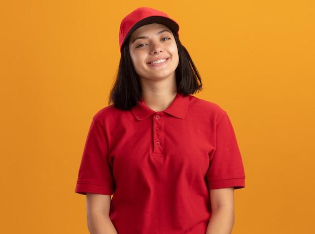 Gelukkig jong leveringsmeisje in rood uniform en glb die vrolijk glimlacht status over oranje muur