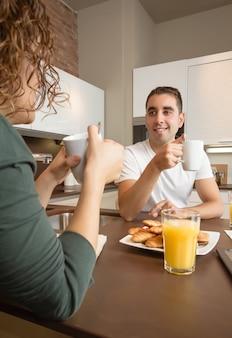 Gelukkig jong liefdespaar dat spreekt en een goed ontbijt heeft in de thuiskeuken