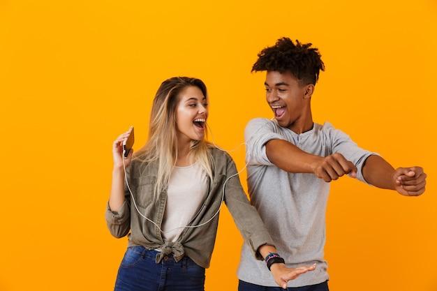 Gelukkig jong liefdevol paar dansen geïsoleerd over gele muur luisteren muziek door oortelefoons