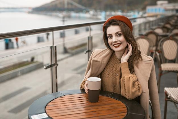 Gelukkig jong meisje dat buiten in een straatrestaurant of op een terras zit en glimlachend wegkijkt met een kopje koffie...